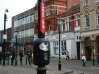 A smartbin attached to a lamp post for cigarette stubbs and chewing gum.